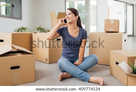 Beautiful smiling woman having a phone call and sitting on the floor of her new house surrounded by cardboard boxes - stock photo