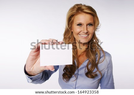 Beautiful smiling woman holding a blank business card. Focus is on card so it is useful to write something on it. - stock photo