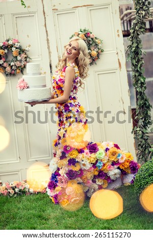 Beautiful smiling woman in a dress with flowers and big cake in hands - stock photo