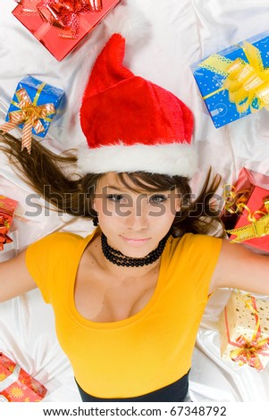Beautiful smiling woman in a santa hat with gift in box