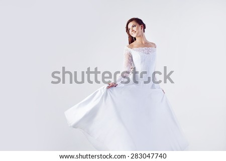 beautiful smiling woman in a wedding dress - stock photo