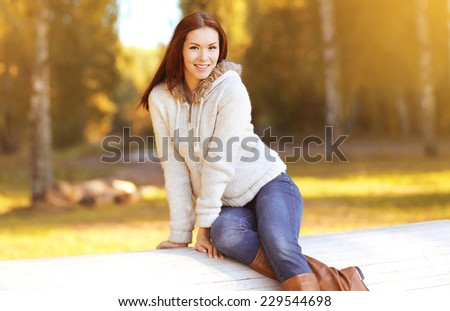 Beautiful smiling woman in autumn clothes outdoors in sunny day - stock photo