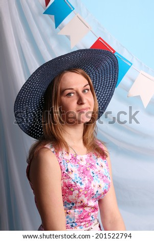 Beautiful smiling woman in blue hat poses in studio with decorations - stock photo