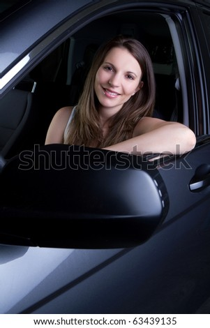 Beautiful smiling woman in car - stock photo