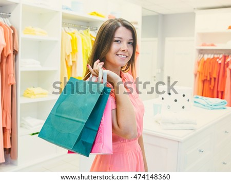 Beautiful smiling woman in dress with long hair shopping, holding shopping bags.Sale, gifts, christmas, holidays and people concept - smiling woman with colorful shopping bags over shop