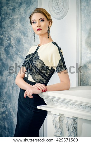 Beautiful smiling woman in elegant evening dress standing by a fireplace in a room with classical vintage interior. Jewellery. Fashion shot. Hairstyle. - stock photo