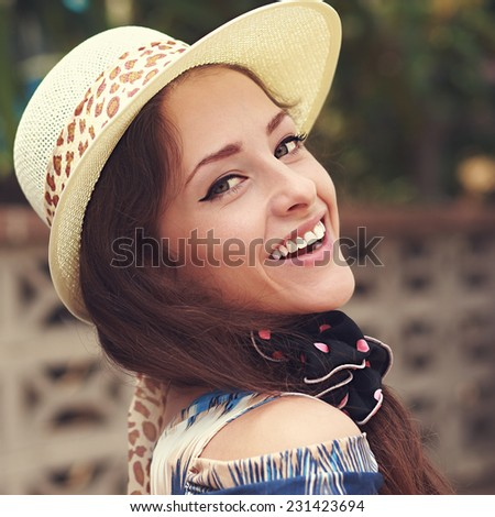 Beautiful smiling woman in hat looking outdoors summer background. Closeup portrait - stock photo