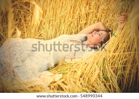 beautiful smiling woman in white dress lying in the field among the ears of wheat. contemplation. instagram image filter retro style
