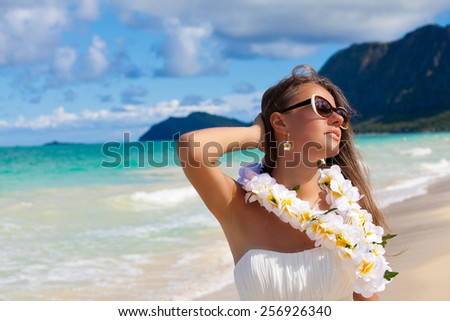 Beautiful smiling woman in white dress posing on the beach with welcoming Lei on the hawaiian island Oahu Island. Summer luxury vacation. - stock photo