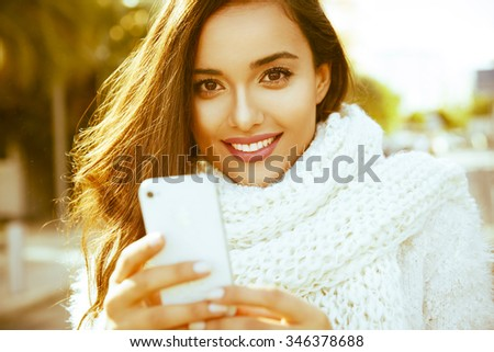 Beautiful smiling woman in winter outfit using her smartphone. Happy woman toned in warm colors. Outdoors shot. Horizontal. - stock photo