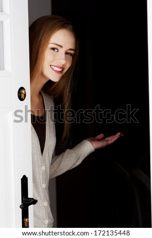 Beautiful smiling woman is opening door and inviting to come in.  - stock photo