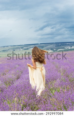 Beautiful smiling woman is wearing wedding dress running at field of purple lavender flowers  - stock photo