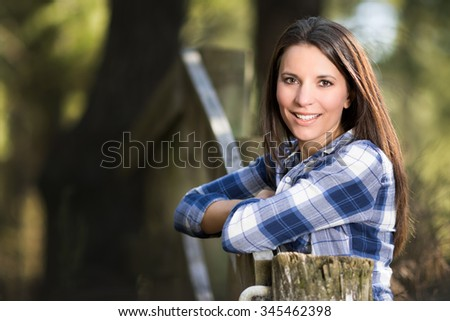 Beautiful smiling woman leaning on fence - stock photo