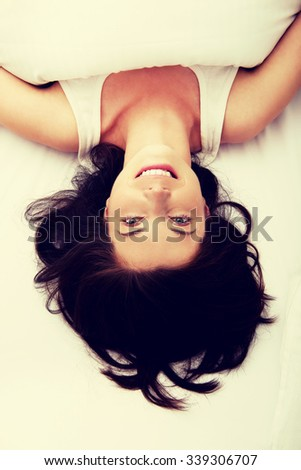 Beautiful smiling woman lying in bed.