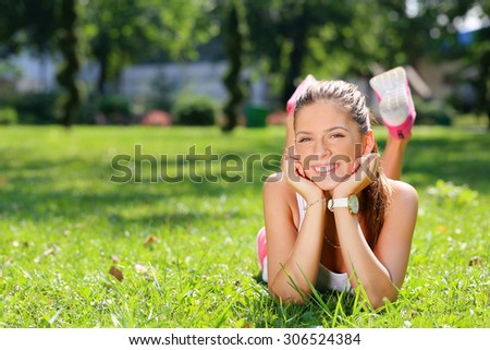 beautiful smiling woman lying on a grass - stock photo