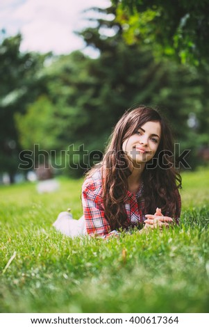 Beautiful smiling woman lying on a grass outdoor. - stock photo