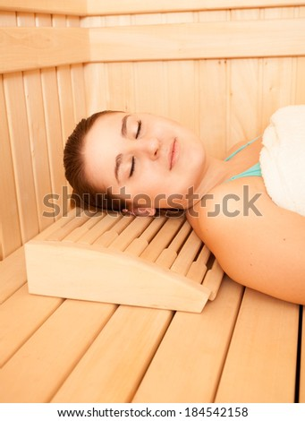 Beautiful smiling woman lying on bench at sauna