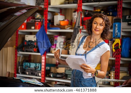 beautiful smiling woman mechanic in blue denim overalls with a laptop and sheets of paper in the interior of an automobile repair shop near the car with an open hood