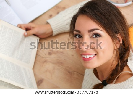 Beautiful smiling woman portrait lying on floor reading book. Female student studying using textbooks. Education, learning, self development, leisure, pastime, library or bookshop concept - stock photo
