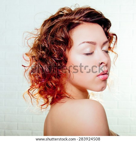 Beautiful smiling woman portrait with red hair on a white background