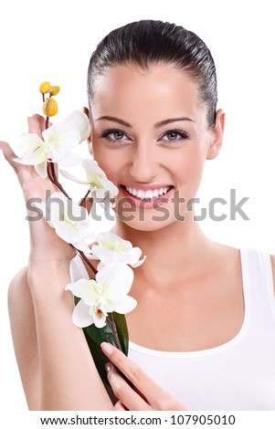 Beautiful Smiling woman posing with white orchid next her face - stock photo