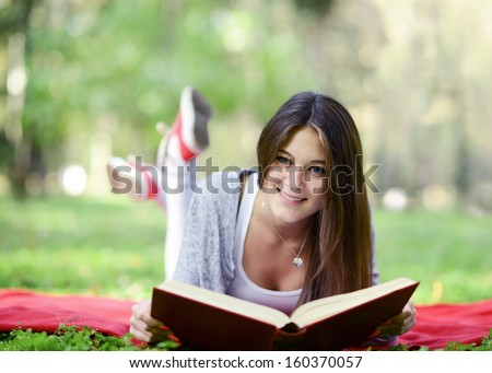 Beautiful smiling woman reading book in park