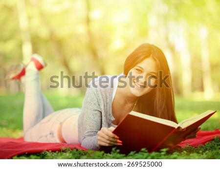 Beautiful smiling woman reading book in park - stock photo