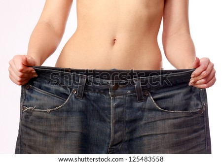 Beautiful smiling woman showing how much weight she lost - Isolated on white - stock photo