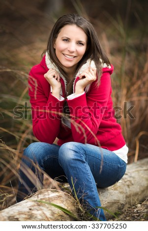 Beautiful smiling woman sitting on log - stock photo