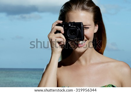 beautiful smiling woman taking photos on the beach blue sky background - stock photo