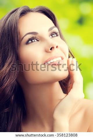 beautiful smiling woman touching skin or applying cream, outdoors - stock photo