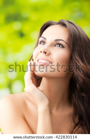 beautiful smiling woman touching skin or applying cream, outdoors - stock photo