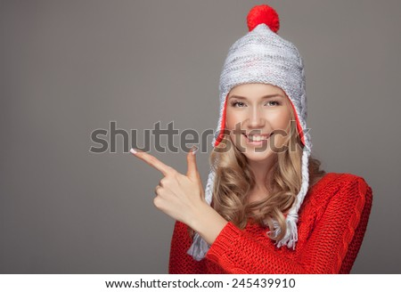 Beautiful smiling woman wearing winter clothing. Pointing on copyspace. - stock photo
