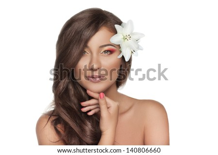 Beautiful smiling woman with a lily in her hair