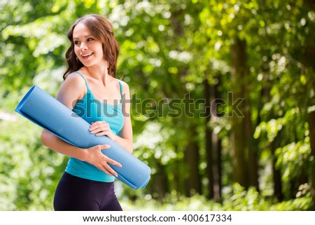 Beautiful smiling woman with a yoga mat outdoors.