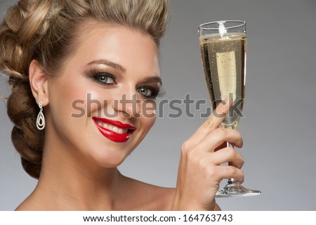 Beautiful smiling woman with fashion bright makeup and hairstyle with a glass of champagne. Party, drinks, christmas concept