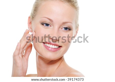 Beautiful smiling woman with good condition of her skin touching her cheek