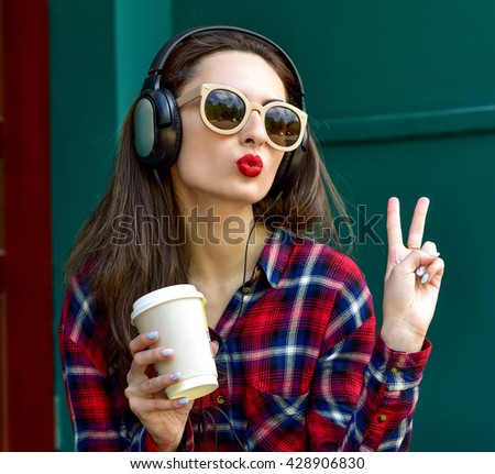 Beautiful smiling woman with headphones listens to music. Blowing lips kiss. Fashion woman in sunglasses outdoor. - stock photo