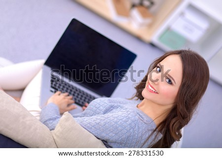 Beautiful smiling woman with laptop and a credit card - stock photo
