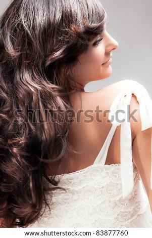 beautiful smiling woman with long wavy hair, profile, studio portrait - stock photo