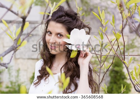 beautiful smiling woman with magnolia flowers.Spring time - stock photo