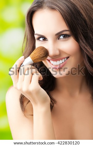 beautiful smiling woman with make up brush, outdoor - stock photo