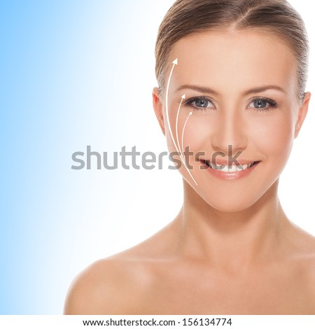 Beautiful smiling woman with naked shoulders with few shafts on her face that are rising up over a white and blue background - stock photo