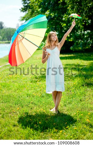 Beautiful smiling woman with two rainbow umbrellas, outdoors