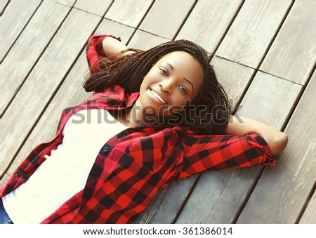 Beautiful smiling young african woman relaxed on wooden floor with hands behind head, wearing a red checkered shirt, top view - stock photo
