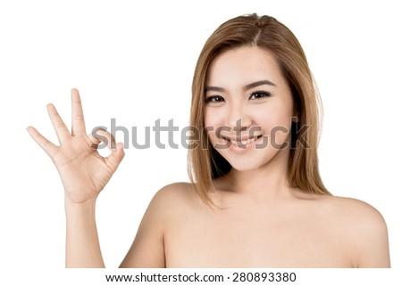 Beautiful smiling young Asian woman showing ok sign - stock photo