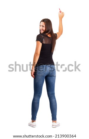 Beautiful smiling young brunette pointing with pencil, back view. Full body length isolated over white.