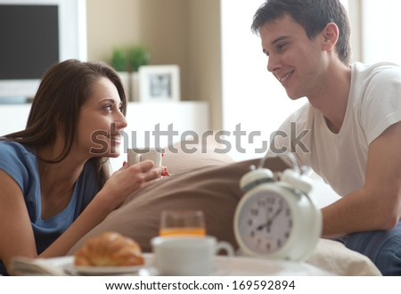 Beautiful smiling young couple having breakfast in bed - stock photo