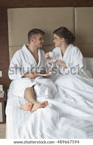 Beautiful smiling young couple having breakfast in bed