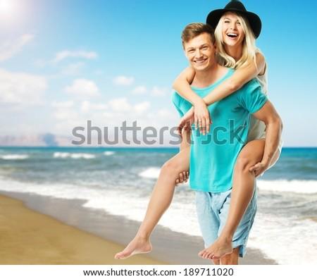 Beautiful smiling young couple having fun on a beach - stock photo